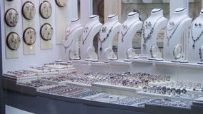 Showcase Store Jeweler Ornaments. Silver rings with precious stones, necklaces on mannequins and various ornaments. Shops with Asian Goods on Soho Square stock video