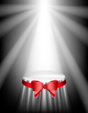 Showcases for your exposure floodlit. Podium covered with a cloth and red bow Royalty Free Stock Photography