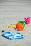 Showels y cubos coloridos de los niños con el tablero que practica surf en la playa arenosa Fotos de archivo libres de regalías