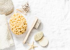 Shower accessories - face brush, sponge, pumice stone, towel, soap on a light background, top view. Cleansing of the skin health c. Oncept. Flat lay royalty free stock photo