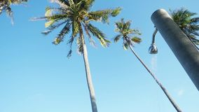 Shower on the beach at the hotel with pouring water against the backdrop of palm trees and the blue sky. Travel concept. Slow motion. 1920x1080, hd stock footage