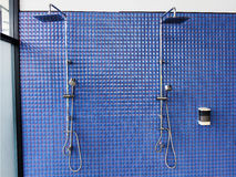 Shower on blue tile wall Stock Image