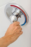 Shower faucet. Human Hand switches a Shower faucet cold and hot water in the bathroom Royalty Free Stock Photos