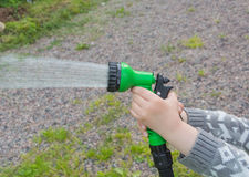 Shower with garden hose watering the lawn. Child watering garden with watering can royalty free stock image