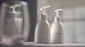 Shower Gel and Shampoo. Cosmetics, moisturizer, two white ceramic bottles with shower gel and shampoo. Set of body and hair care products stock video footage