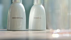 Shower gel and shampoo. Cosmetics, moisturizer, two white ceramic bottles with shower gel and shampoo. Set of body and hair care products stock video