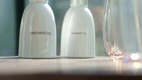 Shower Gel and Shampoo. Cosmetics, moisturizer, two white ceramic bottles with shower gel and shampoo. Set of body and hair care products stock footage