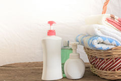 Shower gel with Skin cream and bath towels in basket Royalty Free Stock Photos