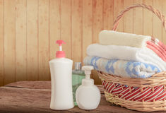 Shower gel with Skin cream and bath towels in basket Stock Photos