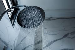 [shower head] shower head in bathroom with water drops flowing.  stock photography