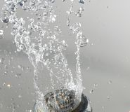 Shower head with water on gray . Stock Photography