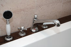 Shower head and water tap. On side of bath tub in luxury room Royalty Free Stock Photography