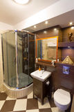 Shower in modern bathroom. Modern brown bathroom interior with brown tiles Royalty Free Stock Images