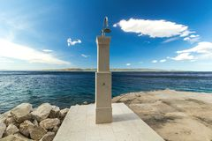 Shower on a rocky beach, blue sea in the background Stock Image