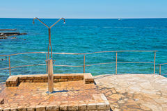 Shower on the rocky beach in Istria. Croatian coast royalty free stock photos