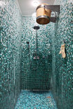 Shower room with blue mosaic in sauna. Shower room with blue mosaic and wooden bucket in sauna stock images
