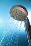Shower with running water. On blue background Royalty Free Stock Photo