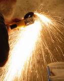 Shower of Sparks. Man using a cut-off grinder to remove steel fasteners from concrete wall Royalty Free Stock Photography