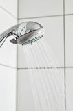 Shower Sprinkler. Activated chrome shower head against a tiled wall Royalty Free Stock Photo