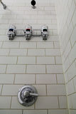 Shower stall and Soap Dispenser. Shower with white tiles including soap dispensers, showerhead and chrome faucet Royalty Free Stock Image