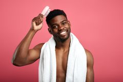 Shower time concept. Macho with white towel on his neck brushing his hair royalty free stock images