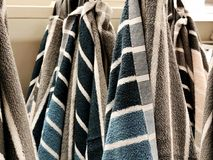 Shower towels. Terrycloth towels in pile for selling. Home decor cloth in department store. Terry towels vertical pile on shelf. Stock Photos