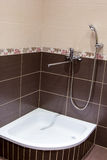 Shower tray in the bathroom lined with brown tiles Royalty Free Stock Photo