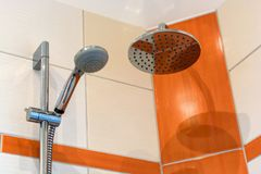 Shower with two shower heads and modern tile mirror. Detail of a shower of different colored tiles and two different shower heads stock photography