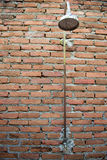 Shower water. On brick background Royalty Free Stock Photos