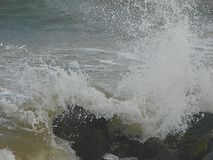Shower of Water Droplets due to Sea Waves Crashing on Rocks Royalty Free Stock Image