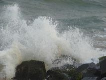 Shower of Water Droplets due to Sea Waves Crashing on Rocks Royalty Free Stock Photos