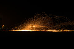 Showers of hot glowing sparks from spinning steel wool. Showers of hot glowing sparks from spinning steel wool yellow royalty free stock photo