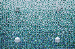 Showers on mosaic tiles. Two showers on the outside wall with beautifull blue, aqua and white mosaic tiles Royalty Free Stock Images