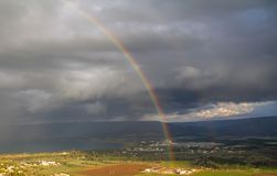 Showers and rainbow over the Sea of Galilee, Israel`s natural water sources, on a winter day with dramatic rain clouds scenery stock photo