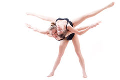 2 showgirls flexible athletic women pretty girl friends raised one another on the back doing split in the air Stock Image