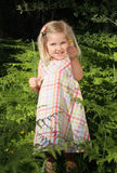 Showing. Excited little blond girl standing amongst ferns in nature and showing yellow wildflowers she has picked Stock Photos