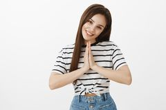Showing all feminine sides of charachter to receive what she wants. Good-looking european female, holding hands in pray. Tilting head with cute smile, wanting stock image