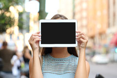 Showing a blank tablet screen covering her face Stock Photo