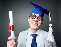 Showing certificate. Portrait of funny student in eyeglasses holding graduation certificate and looking at camera Stock Photo