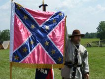 Showing the Confederate Flag. Photo of a man dressed as a confederate soldier showing one of the many varieties of the confederate flag at the henry house on Royalty Free Stock Image
