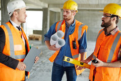 Showing Construction Site to Inspector. Group of three workmen wearing protective helmets and vests standing among concrete walls on construction site discussing Stock Photos