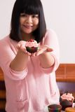 Showing a cupcake. Young Asian girl showing a cupcake Royalty Free Stock Image