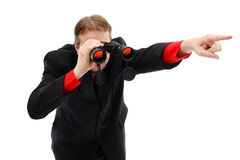 Showing direction with binoculars. Man looking through binoculars and showing the right direction Stock Photos