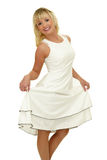 Showing dress. Smiling young blond model with long curly hair pulling her white dress up Royalty Free Stock Photos