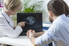 Showing fetus ultrasound. Gynecologist showing to young married couple fetus ultrasound Stock Photo