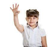 Showing four fingers. Cheerful happy young schoolgirl showing four fingers Royalty Free Stock Images