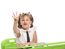 Showing four fingers. Female pupil sitting at the desk and showing four fingers Stock Photo