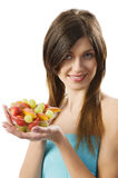 Showing fruit salad. Nice young woman showing a salad fruit and looking in camera smiling Royalty Free Stock Photo