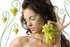 Showing grape. Pretty girl with bodypaint on shoulder and face looking down with grape Royalty Free Stock Photo