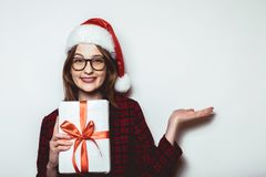 Showing hand Christmas sale, Young girl in Santa Hat on red plai Stock Photos